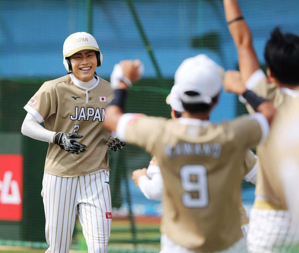 Japan's Saki Yamazaki, left, is celebrated by her teammates after hitting inside-the-park home run in the third inning during their women's world soft