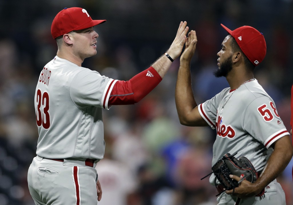 Philadelphia Phillies' Justin Bour, left, celebrates with closing pitcher Seranthony Dominguez after the Phillies defeated the San Diego Padres 5-1 in