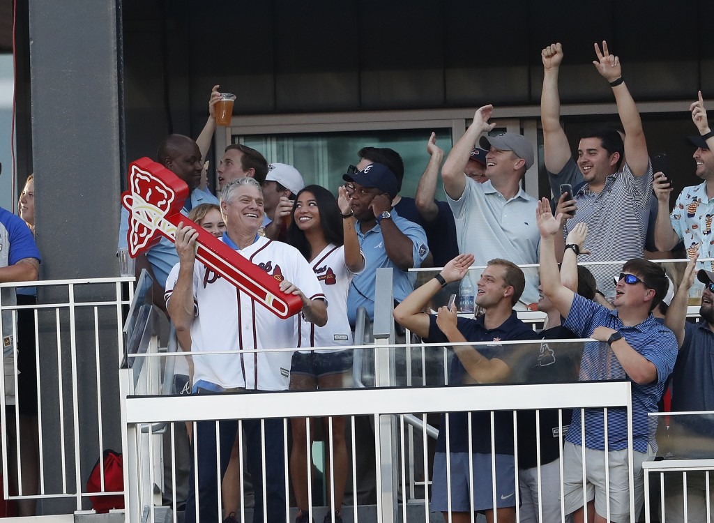 Former Atlanta Braves player Dale Murphy leads the crowd in the first tomahawk chop of the night during the first inning of a baseball game against th