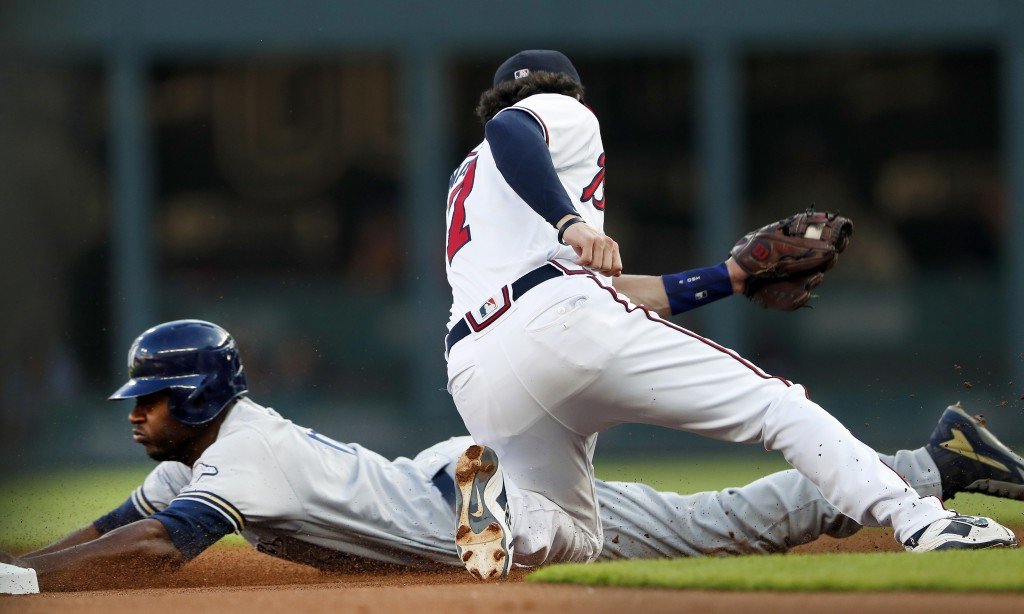 Milwaukee Brewers' Lorenzo Cain, left, steals second base as Atlanta Braves shortstop Dansby Swanson (7) applies a late tag in the first inning of a b