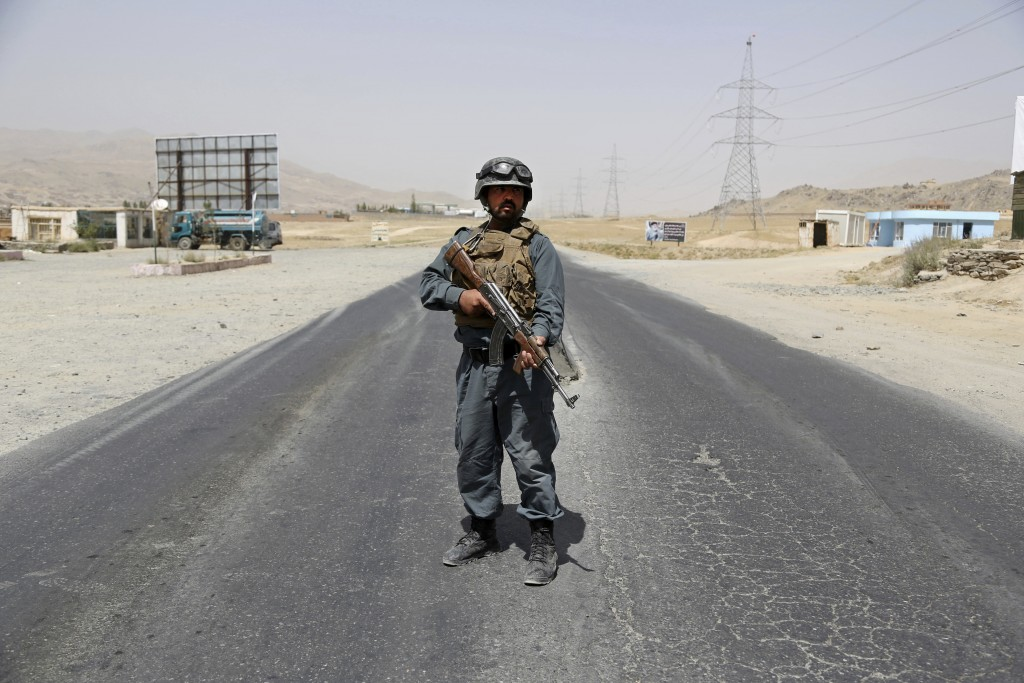 An Afghan Police officer mans a checkpoint on the Ghazni highway, in Maidan Shar, west of Kabul, Afghanistan, Monday, Aug. 13, 2018. Afghan Defense Mi...