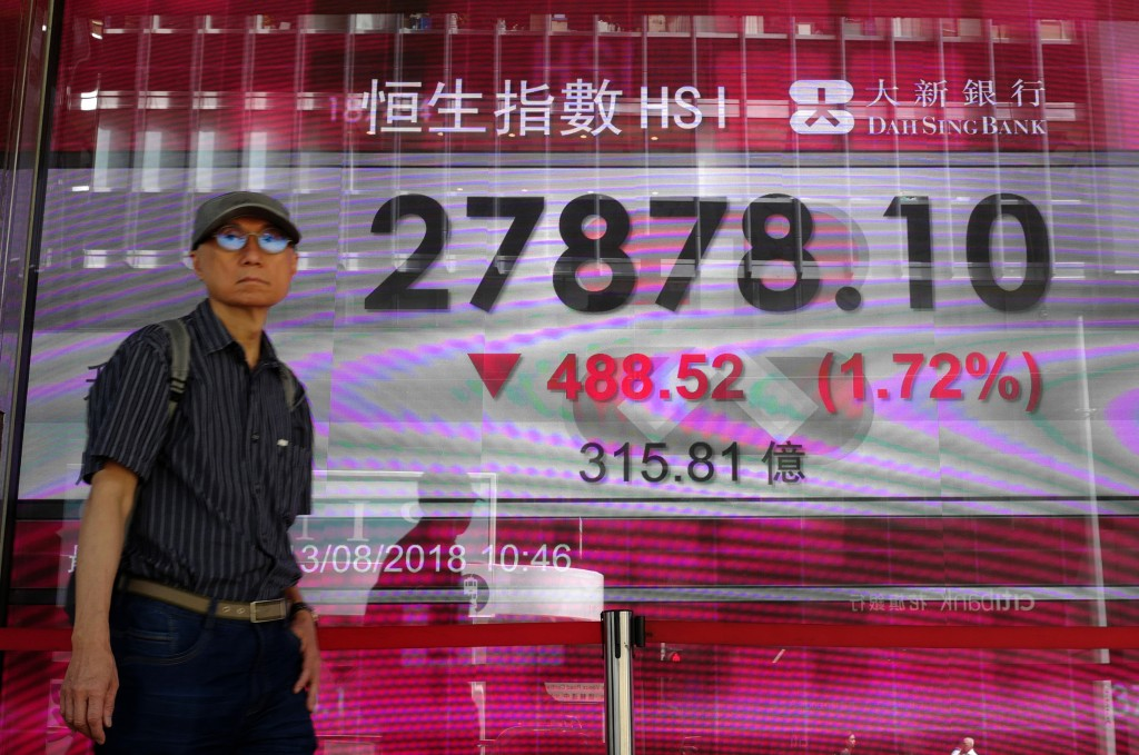 A man walks past a bank electronic board showing the Hong Kong share index outside a Hong Kong local bank Monday, Aug. 13, 2018. Asian stock prices sa...