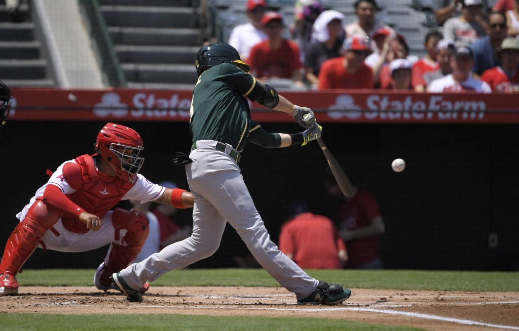 Oakland Athletics' Jed Lowrie, right, hits a double for his 1,000th career hit as Los Angeles Angels catcher Francisco Arcia watches during the first