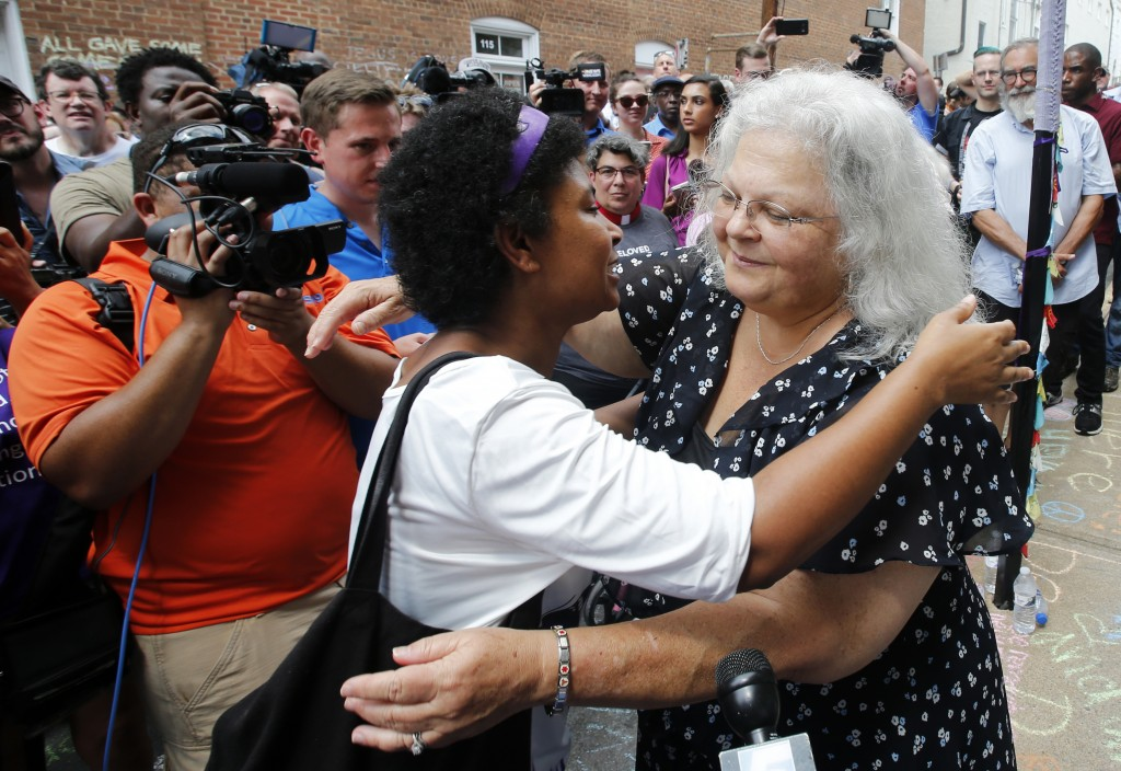 Susan Bro, right, mother of Heather Heyer who was killed during last year's Unite the Right rally, embraces a supporter after laying flowers at the sp...
