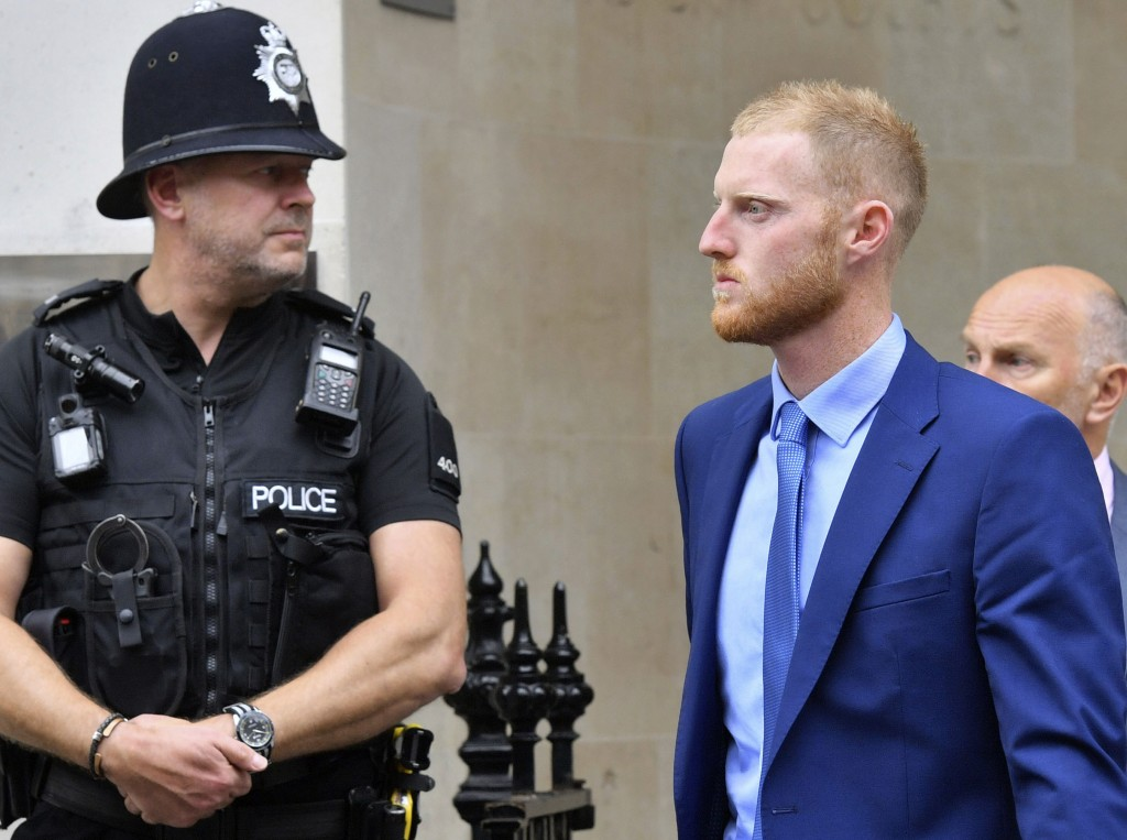 England cricketer Ben Stokes, right, walks out of Bristol Crown Court, during a lunch break where he is on trial accused of affray, in Bristol, Englan...