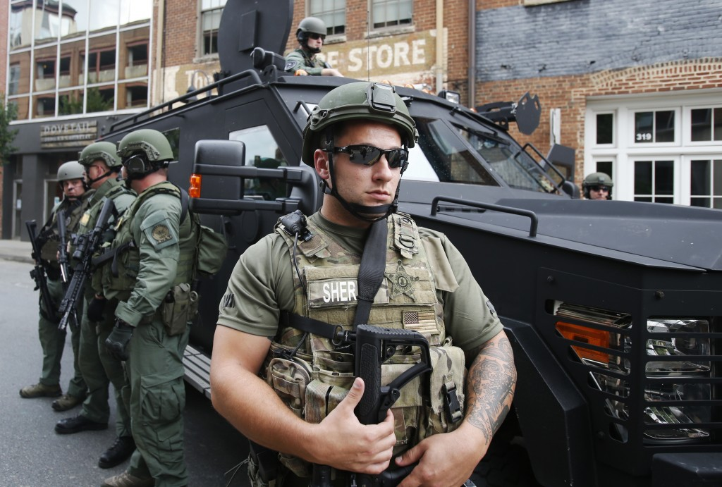 Members of a SWAT team keep an eye on demonstrators marking the one year anniversary of the Unite The Right rally in Charlottesville, Va., Sunday, Aug...