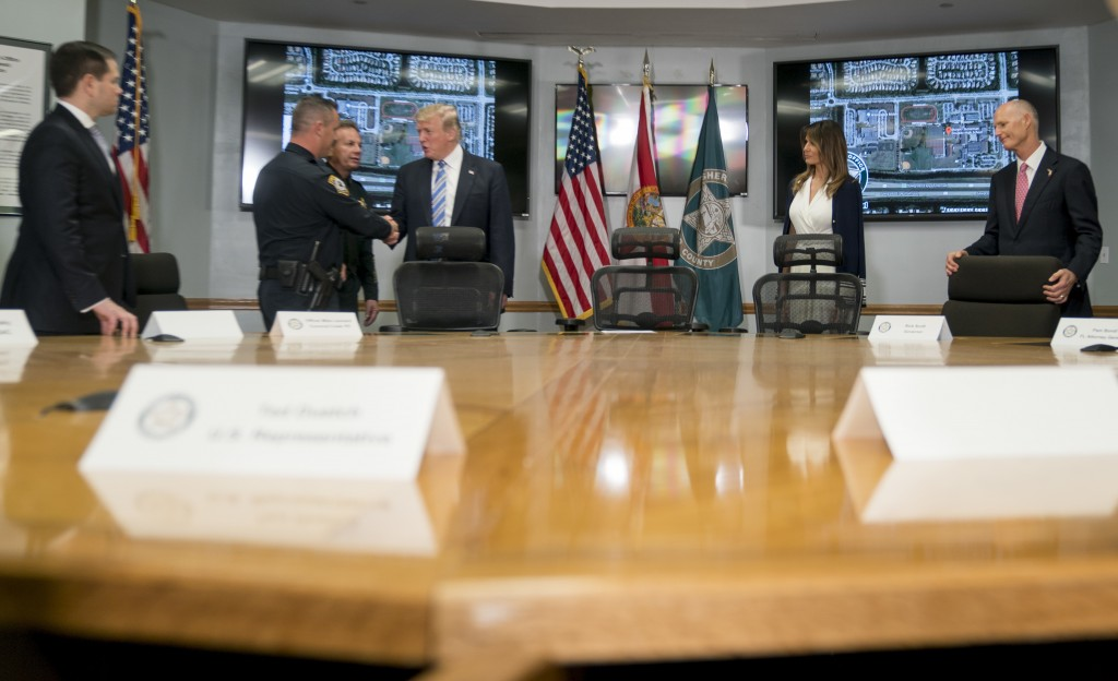 FILE - In this Feb. 16, 2018, file photo, President Donald Trump, third from right, shakes hands with Coconut Creek Police Officer Mike Leonard, secon...