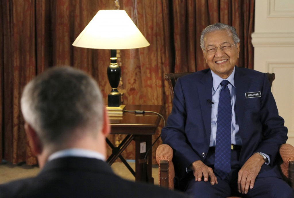 Malaysia's Prime Minister Mahathir Mohamad, right, is interviewed in Putrajaya, Malaysia, Monday, Aug. 13, 2018. Mahathir said he will seek to cancel ...