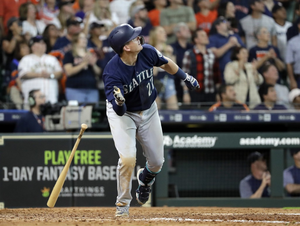 Seattle Mariners' Ryon Healy drops his bat after hitting a home run against the Houston Astros during the ninth inning of a baseball game Sunday, Aug.