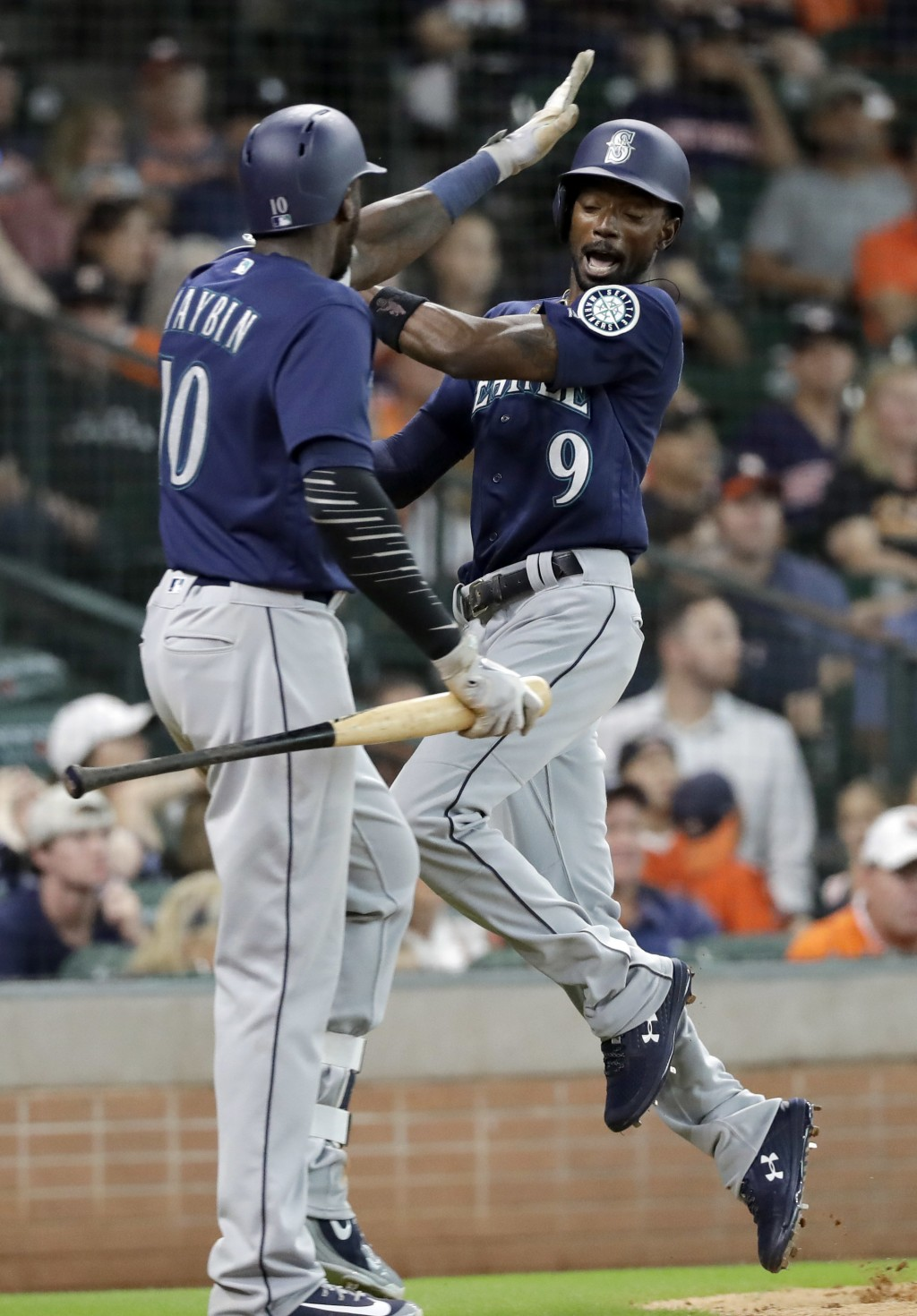 Seattle Mariners' Dee Gordon (9) celebrates with Cameron Maybin (10) after scoring against the Houston Astros during the 10th inning of a baseball gam