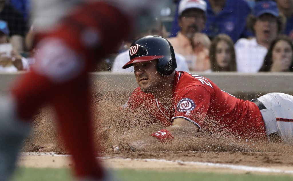 Washington Nationals' Ryan Zimmerman scores on a sacrifice fly by Mark Reynolds during the second inning of a baseball game against the Chicago Cubs, ...