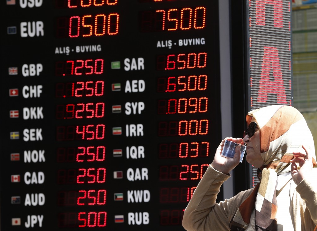 A woman checks the currency exchange rates at a currency exchange shop in Istanbul, Monday, Aug. 13, 2018. Turkey's central bank announced a series of...