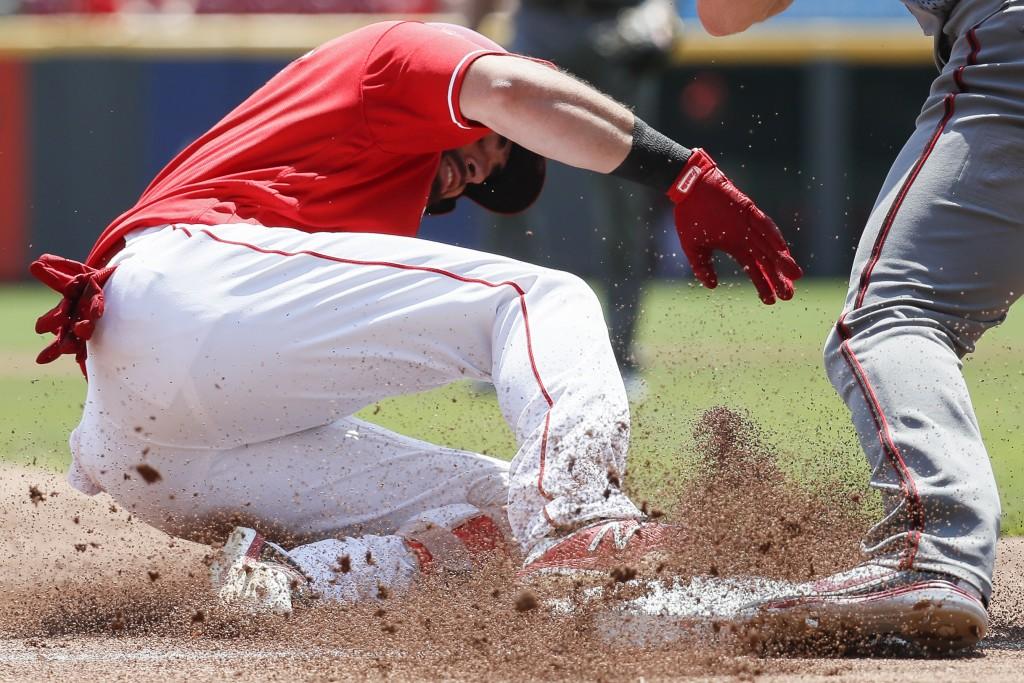 Cincinnati Reds' Jose Peraza slides into third on a triple hit off Arizona Diamondbacks starting pitcher Zack Godley in the third inning of a baseball
