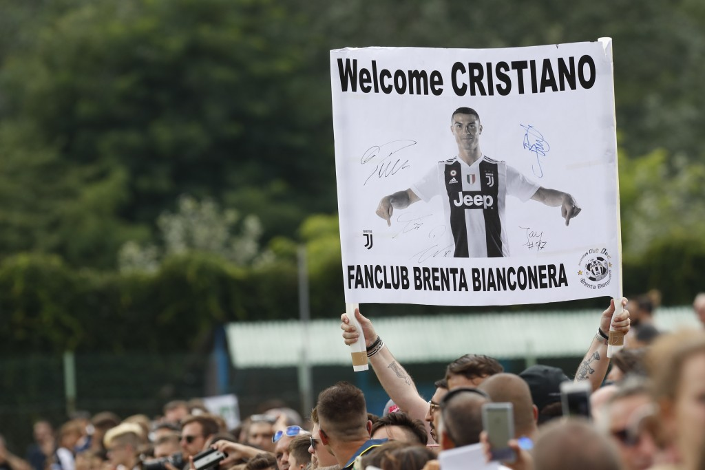 Supporters hold a banner welcoming Juventus' Cristiano Ronaldo as he arrives at Villar Perosa, northern Italy, Sunday, Aug.12, 2018, to take part in a