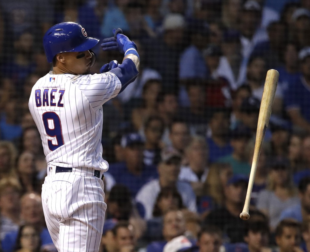 Chicago Cubs' Javier Baez throws his bat after striking out swinging during the third inning of a baseball game against the Washington Nationals, Sund...