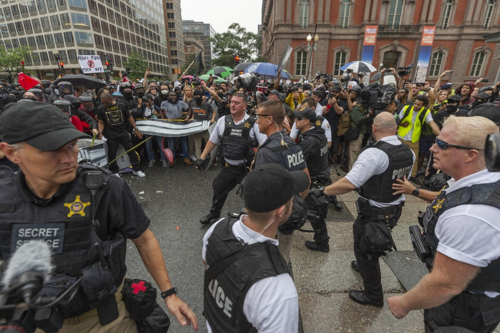 Metro Police and Secret Service personnel are forced back by counter-protesters outside of the Pennsylvania Avenue security barrier on 17th street whi...