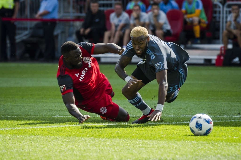 Toronto FC forward Jozy Altidore, left, and New York City FC defender Sebastien Ibeagha, right, go down after becoming entangled while fighting for th