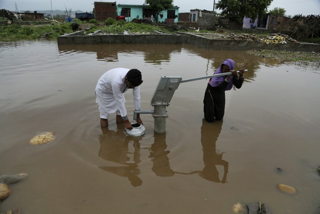 Indians collect drinking water from a hand pump at a flooded street following monsoon rains in Jammu, India, Monday, Aug.13, 2018. India's monsoon sea...