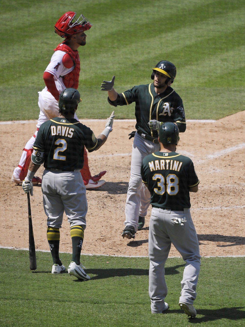Oakland Athletics' Jed Lowrie, top right, is congratulated by Khris Davis (2) and Nick Martini (38) after hitting a two-run home run as Los Angeles An