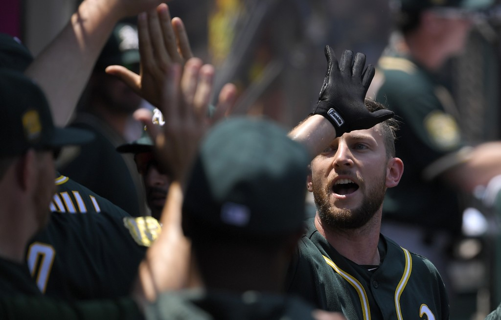 Oakland Athletics' Jed Lowrie is congratulated by teammates in the dugout after scoring on a single by Matt Olson during the first inning of a basebal