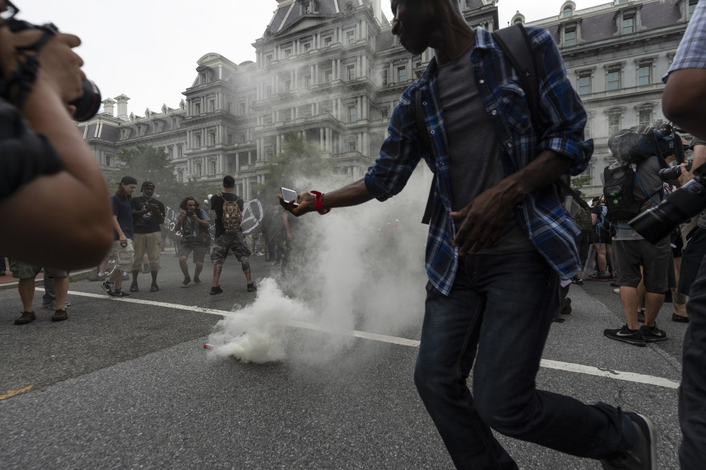 "Journalists photograph a type of smoke grenade placed by Antifa-activists in the middle of 17th street during the ""Unite the Right 2"" rally in Washing"