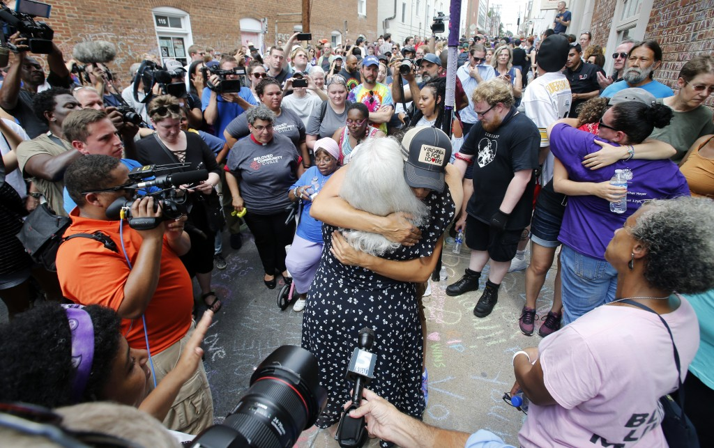 Susan Bro, center back to camera, mother of Heather Heyer who was killed during last year's Unite the Right rally, embraces a supporter after laying f...