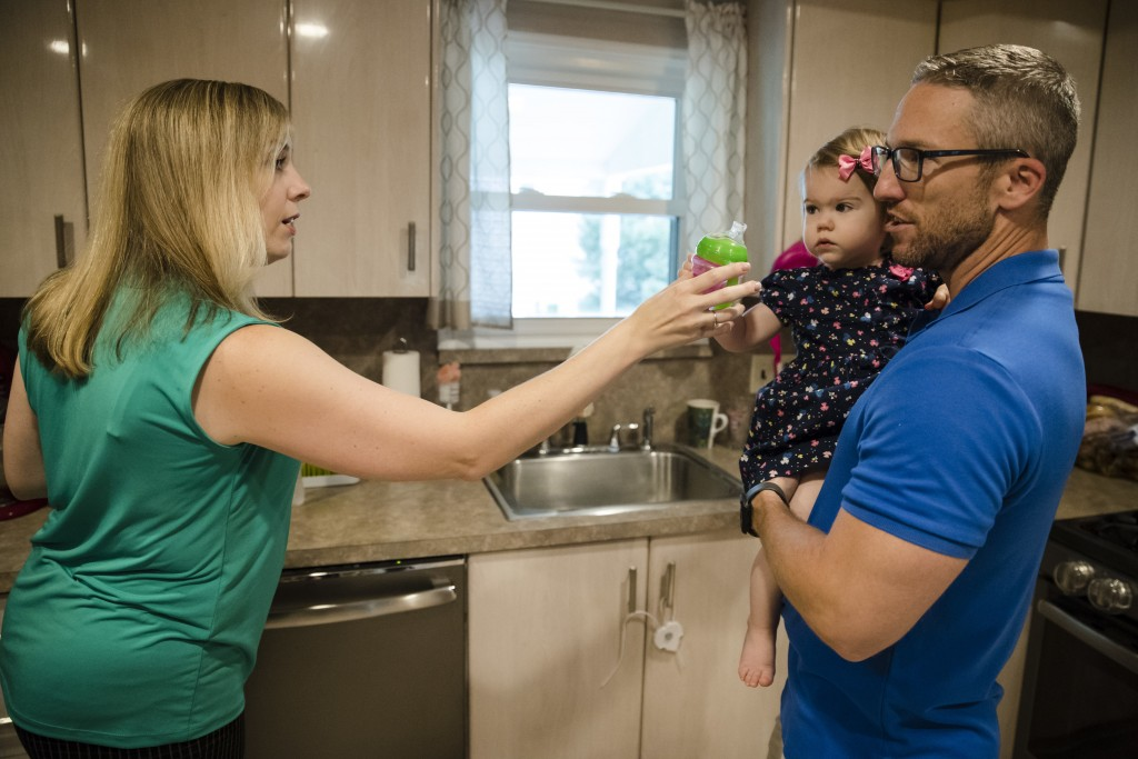 In this Aug. 1, 2018 photo, Lauren Woehr hands her 16-month-old daughter Caroline, held by her husband Dan McDowell, a cup filled with bottled water a...