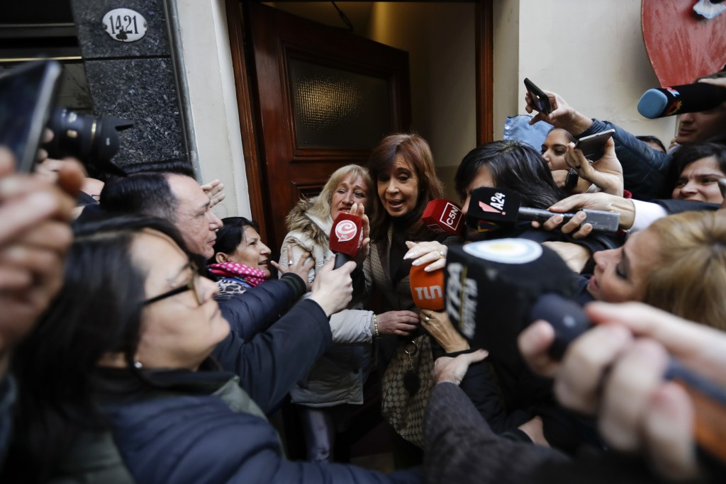 Former President Cristina Fernandez is surrounded by media outside her home as she leaves for a court hearing, in Buenos Aires, Argentina, Monday, Aug...