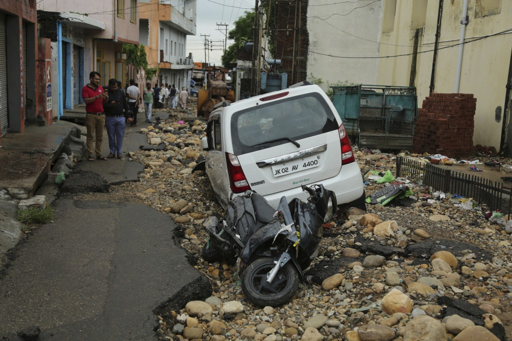 Residents look at the remains of their road and vehiclesdamaged in flash floods following monsoon rains in Jammu, India, Monday, Aug.13, 2018. India's...