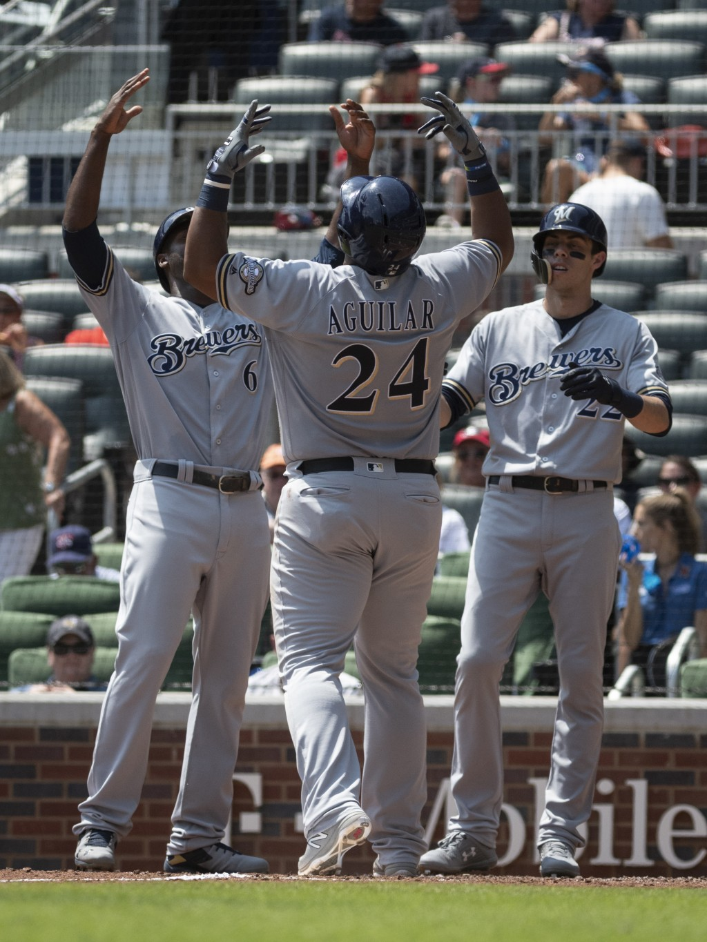 Milwaukee Brewers' Jesus Aguilar (24) celebrates his three-run home run with Lorenzo Cain and Christian Yelich, right, as he crosses home plate during