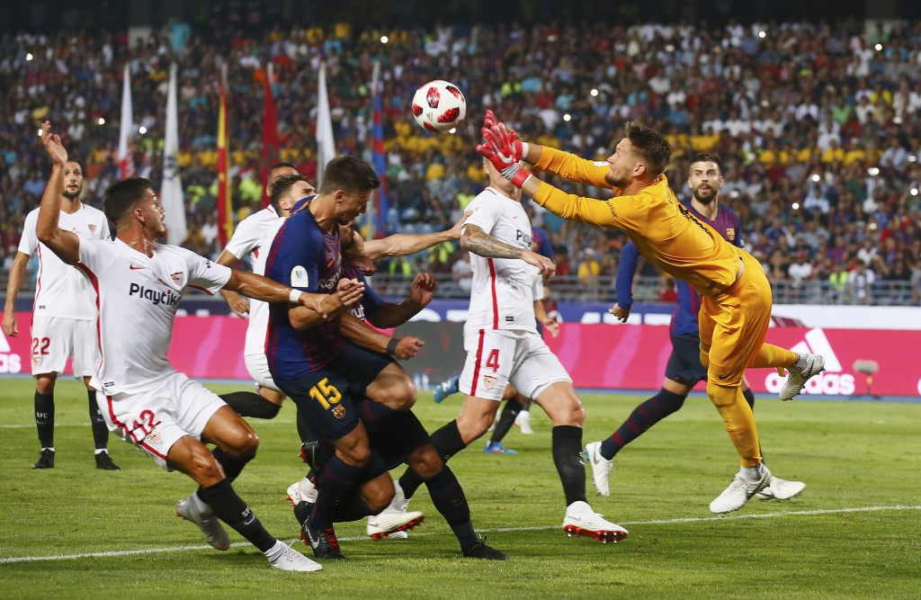 Sevilla goalkeeper Tomas Vaclik, right, leaps for a save during the Spanish Super Cup soccer match between Sevilla and Barcelona in Tangier, Morocco,