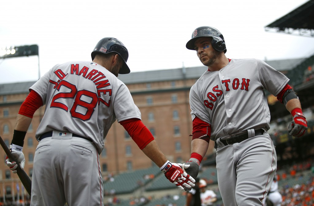 Boston Red Sox's Steve Pearce, right, greets teammate J.D. Martinez after rounding the bases on a solo home run in the first inning of a baseball game