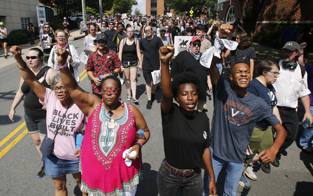 Demonstrators against racism march along city streets as they mark the anniversary of last year's Unite the Right rally in Charlottesville, Va., Sunda...