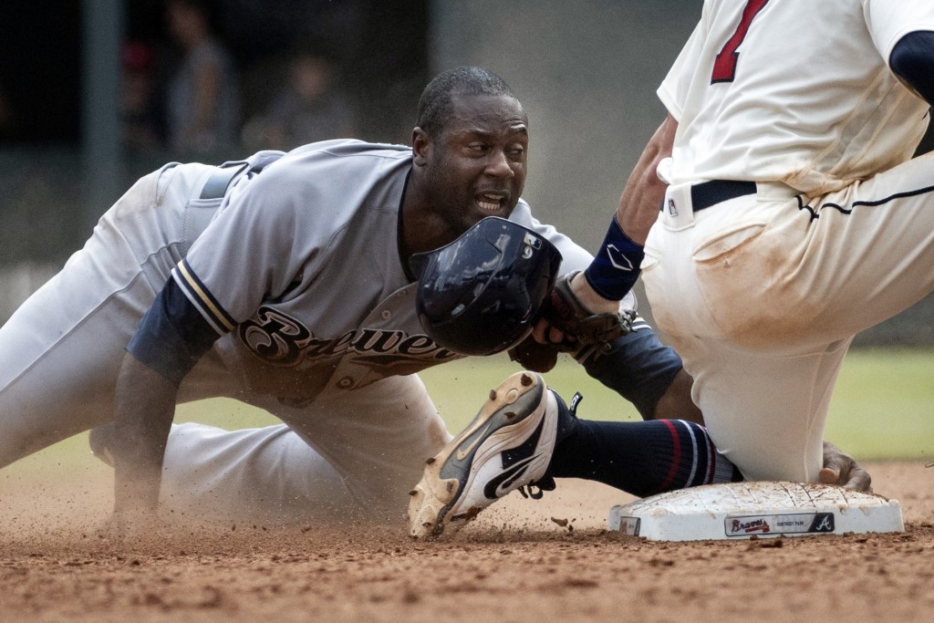 Milwaukee Brewers' Lorenzo Cain loses his helmet while trying to steal second base during the fifth inning of a baseball game against the Atlanta Brav