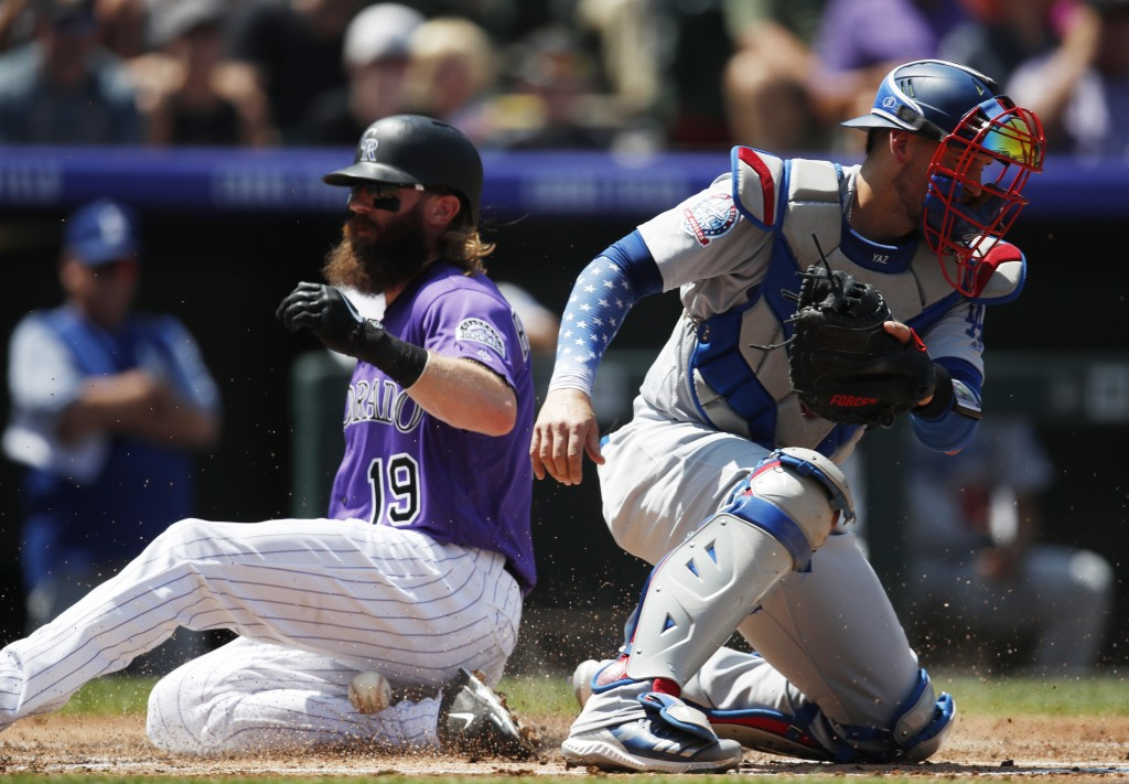 Los Angeles Dodgers catcher Yasmani Grandal, front, misses the throw as Colorado Rockies' Charlie Blackmon scores on a sacrifice fly hit by Trevor Sto