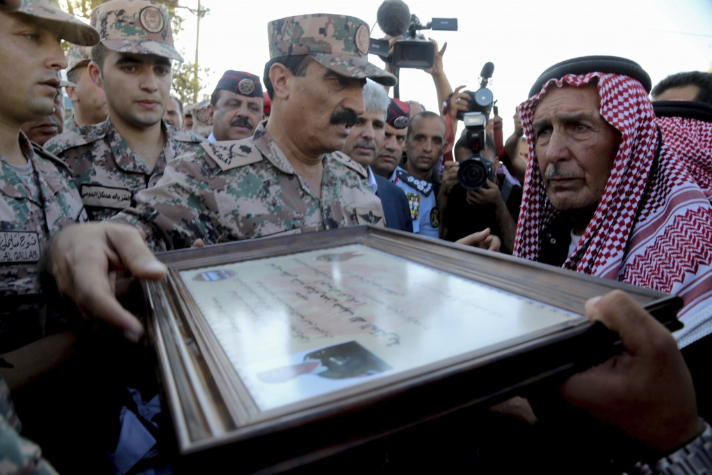 Jordanian soldiers present a certificate and condolences to the father of Sergeant Hisham al-Agarbeh, who was killed during an attack in the predomina...