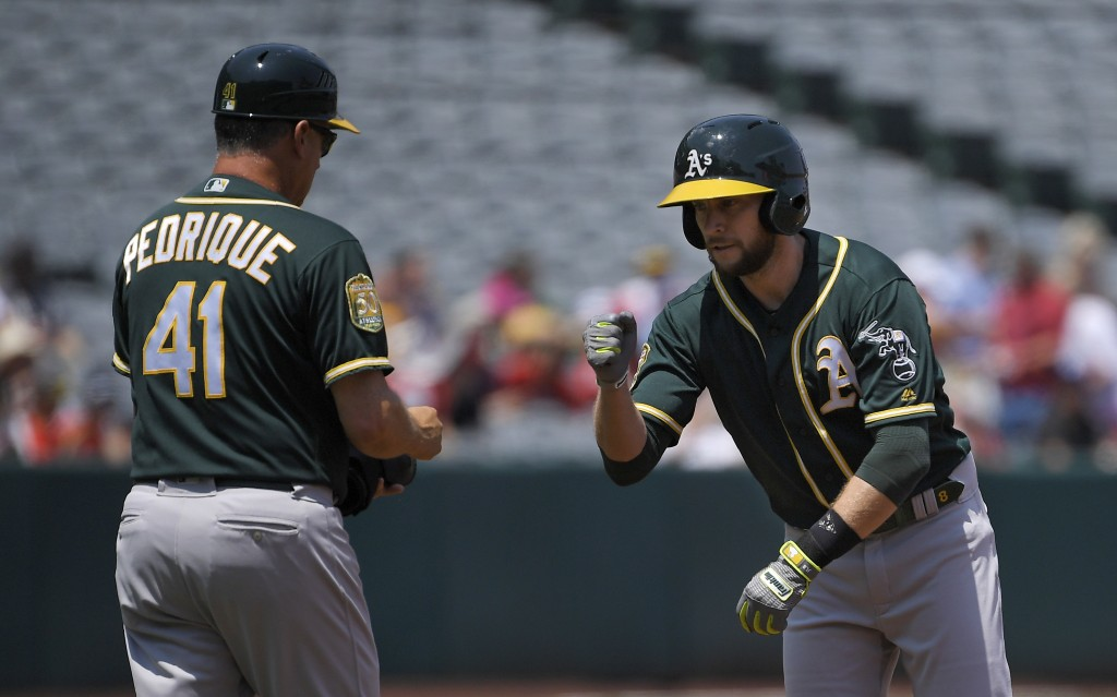 Oakland Athletics' Jed Lowrie, right, is congratulated by first base coach Al Pedrique after hitting a double for his 1,000th career hit during the fi