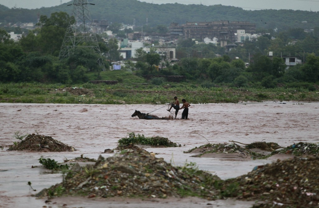Indian nomads on a horse cart try to cross River Tawi that was flooded following monsoon rains in Jammu, India, Monday, Aug.13, 2018. India's monsoon