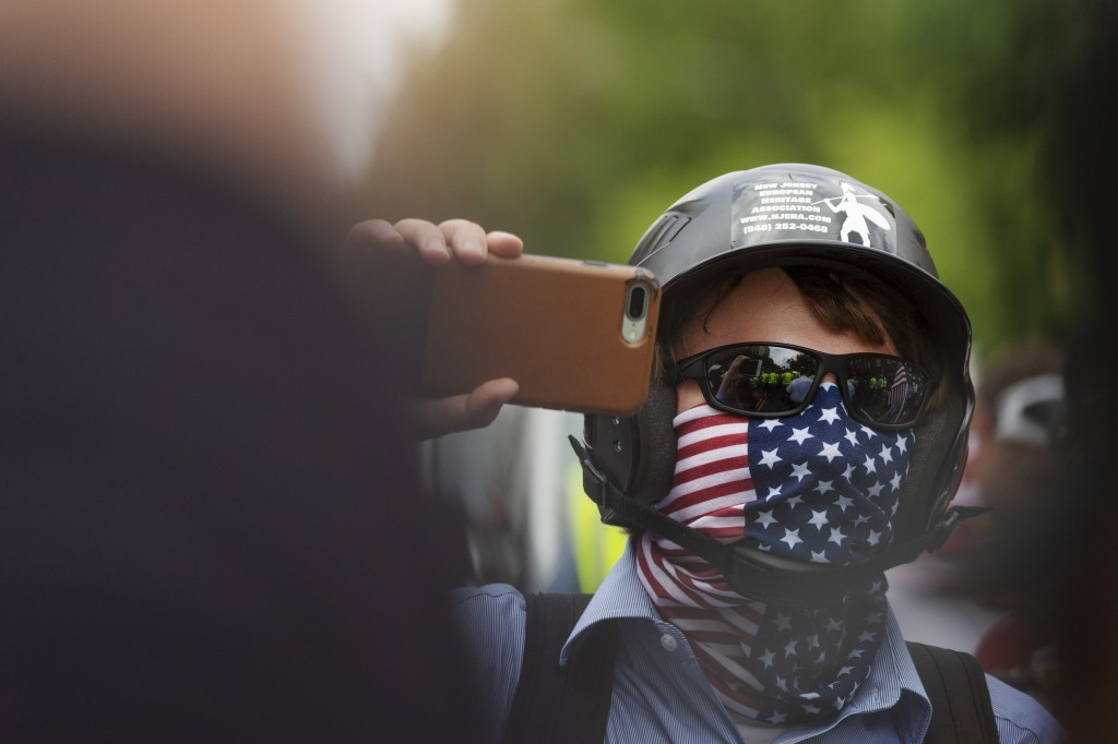 "A white nationalist holds his phone while marching to Lafayette Square during the ""Unite the Right 2"" rally in Washington, Sunday, Aug. 12, 2018. (Cra"
