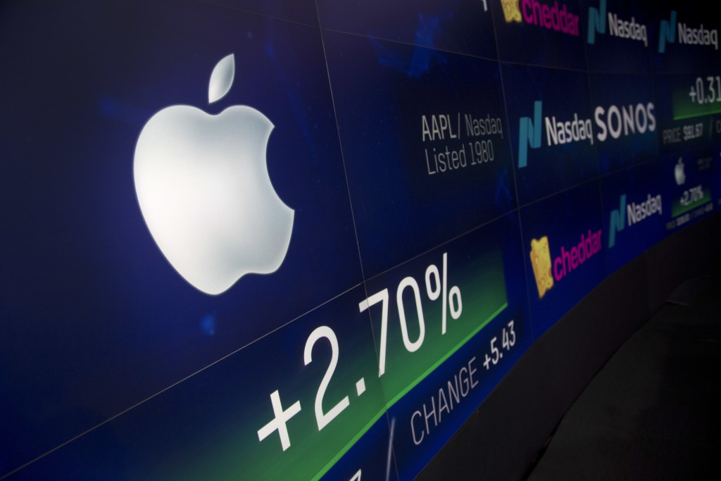 FILE- In this Aug. 2, 2018, file photo an electronic screen displays Apple stock at the Nasdaq MarketSite in New York. Warren Buffett resisted investi...
