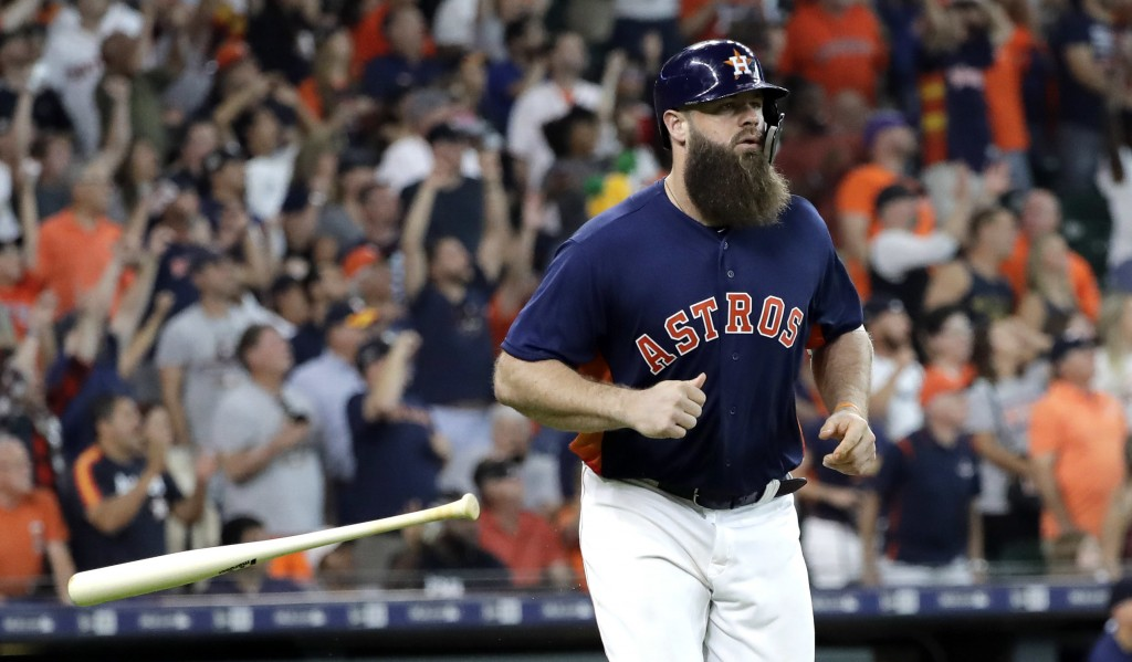 Houston Astros' Evan Gattis tosses his bat after hitting a sacrifice fly to score Alex Bregman from third during the eighth inning of a baseball game
