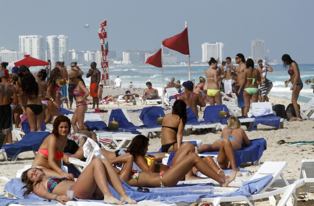 FILE - In this March 10, 2012 file photo, people fill the beach during Spring Break in Cancun, Mexico. Almost 7 million international tourists visit t...