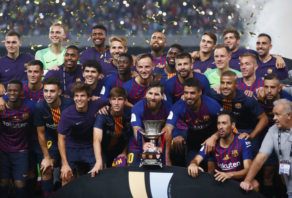 Barcelona players pose with the trophy after winning the Spanish Super Cup soccer match between Sevilla and Barcelona in Tangier, Morocco, Sunday, Aug...