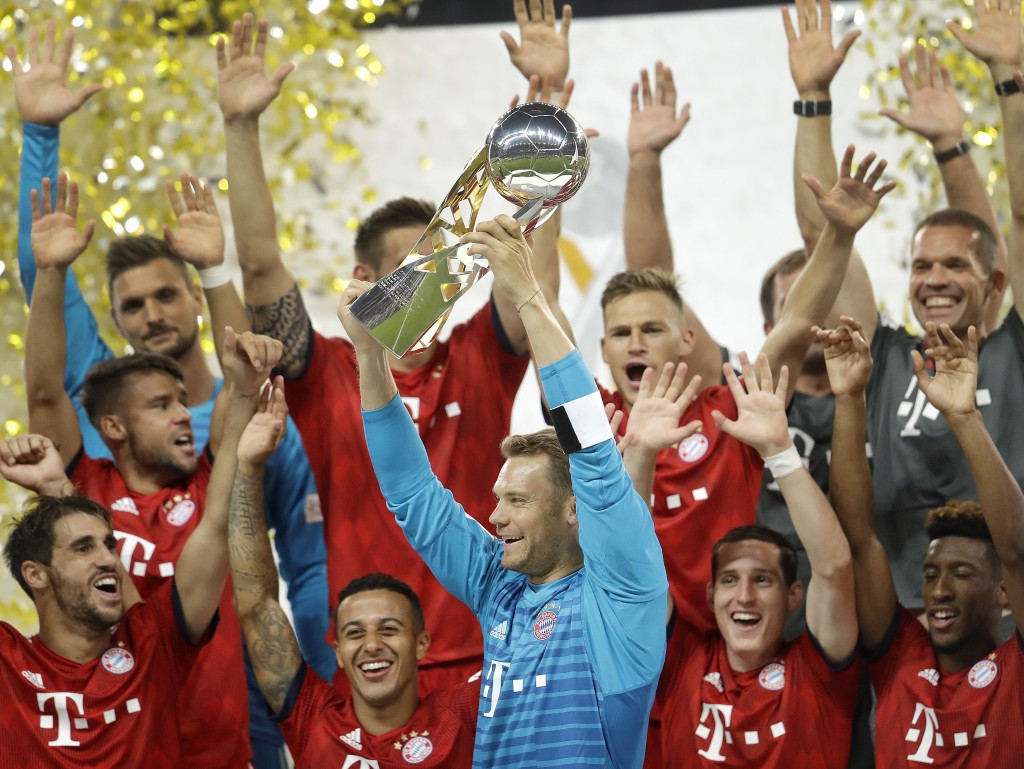 Munich players celebrate with the trophy after a soccer Supercup match between Eintracht Frankfurt and Bayern Munich In Frankfurt, Germany, Sunday, Au
