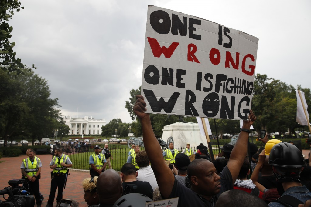 """Demonstrators march near the White House on the one year anniversary of the Charlottesville """"Unite the Right"""" rally, Sunday, Aug. 12, 2018, in Washing..."""