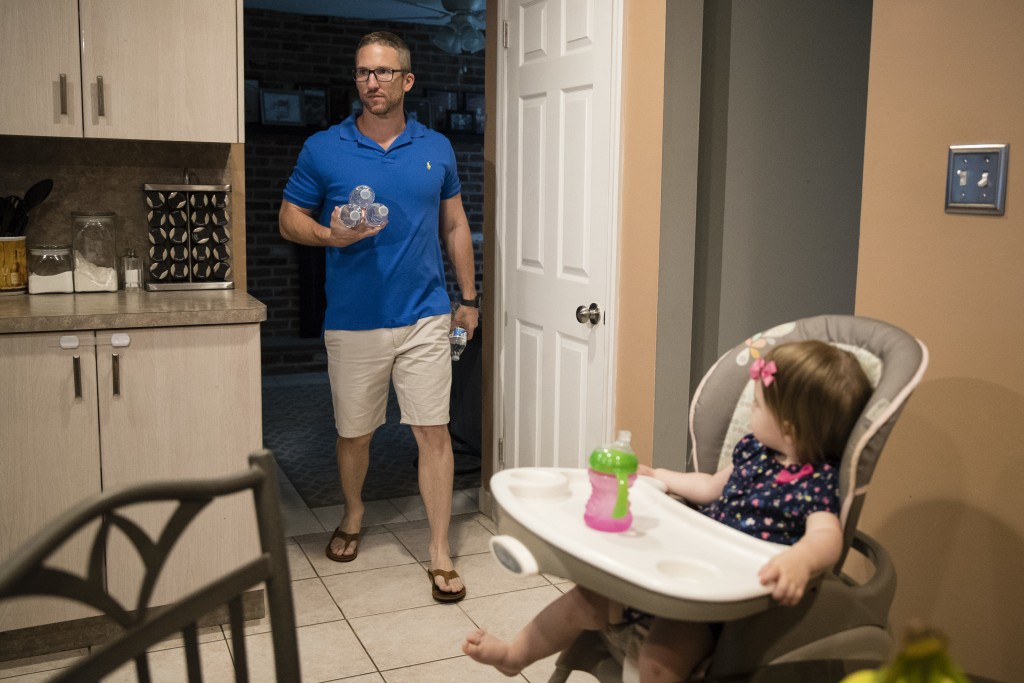In this Aug. 1, 2018 photo, Dan McDowell carries water to his refrigerator as his 16-month-old daughter Caroline, looks on at their home in Horsham, P...