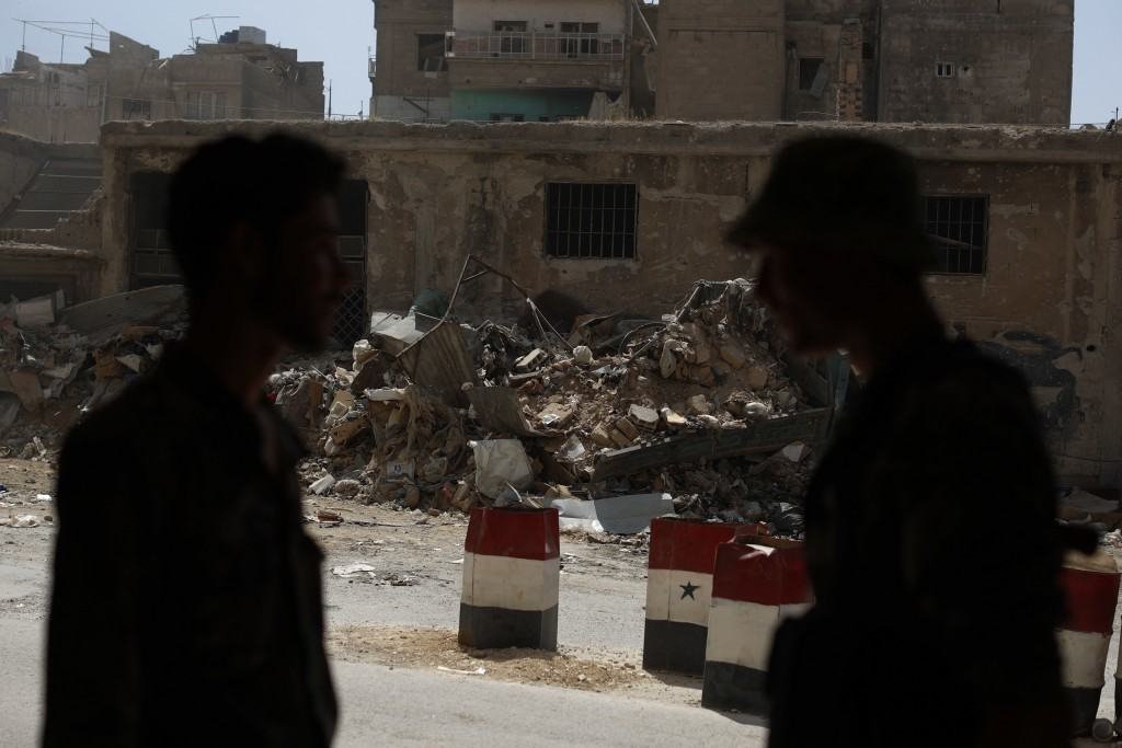 In this July 15, 2018 photo, Syrian soldiers speak as they stand at a checkpoint in the town of Douma, in the eastern Ghouta region, near the Syrian c...