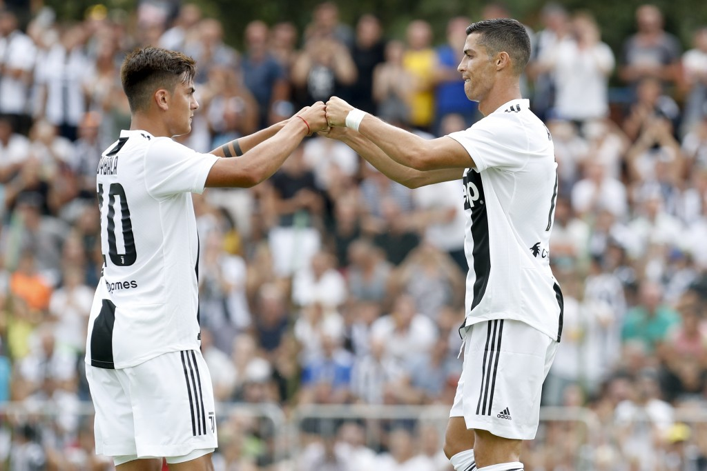 Juventus' Cristiano Ronaldo, right, touches hands with his teammate Paulo Bybala during a friendly match between the Juventus A and B teams, in Villar