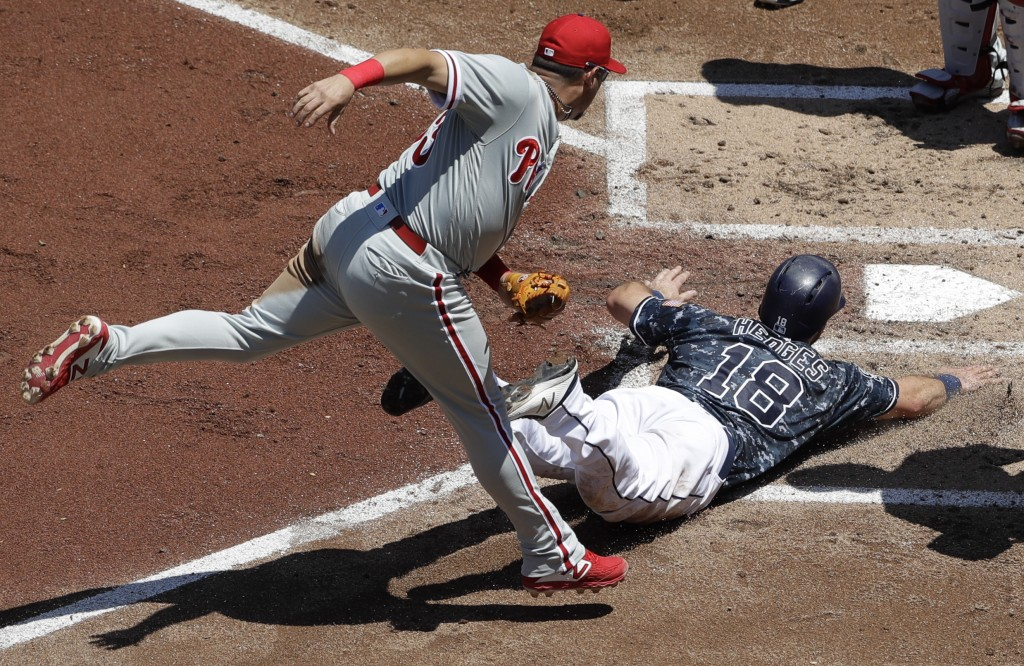 Philadelphia Phillies second baseman Asdrubal Cabrera, left, leaps over San Diego Padres' Austin Hedges, right, after tagging Hedges out while he was