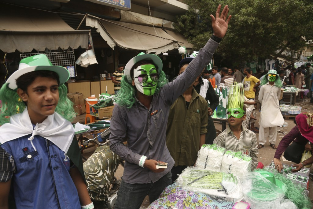 A Pakistani vendor sells national flags, badges and related merchandise to celebrate the 71st Independence Day, in Karachi, Pakistan, Monday, Aug. 13,...